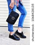 Small photo of Fashion blogger outfit details. Street style fashion girl walking ,wearing blue jeans black shoe lace shoes holding small handbag with details