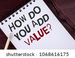 Small photo of Text sign showing How Do You Add Value Question. Conceptual photo Bring business progress contribute earn written Notepad the Wooden background Pencil and Glasses next to it.