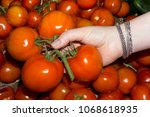 Small photo of woman buyer chooses tomatoes on the counter, only her hand is visible