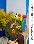 Small photo of Artist in blue sweater draws mixes oil paints with palette knife close-up. He holds palette and brush bristle. Flowers in the background