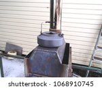 Small photo of Handmade stainless steel wood stove for surviving, heating of home, tent, sauna and cooking, heated with boiling kettle on the top