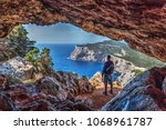 hiker with backpack by a cave... | Shutterstock . vector #1068961787