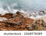 waves are crashing onto seaweed ... | Shutterstock . vector #1068978389