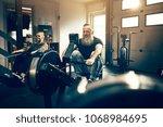 fit mature man with a beard... | Shutterstock . vector #1068984695