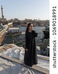 Small photo of Woman dressed in abaya walking near old boats