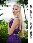 Outdoor portrait of beautiful blond woman in purple dress - stock photo