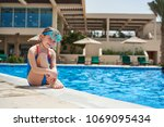 child in a swimsuit in the pool ... | Shutterstock . vector #1069095434