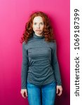 Small photo of Cute young redhead woman pulling a goofy face with wide eyed stare as she stands over a bright pink studio background