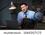 young employee working overtime ... | Shutterstock . vector #1069207175