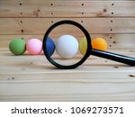 Small photo of Conceptual image. Colourful ping pong ball on wooden pallet. There are racist on colour. Focus on white.