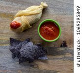 Small photo of Tamale served with blue corn tortilla, tomatillos, tomato sauce and chili pepper top view
