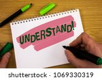 Small photo of Conceptual hand writing showing Understand Motivational Call. Business photo text Know Perceive the meaning of something written by Man on Notepad holding Marker on wooden background Pen.