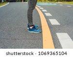 female runner tying her shoes... | Shutterstock . vector #1069365104