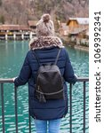 Small photo of Young female tourist in Interlaken, Switzerland back view - looking at the clear water of Aare river