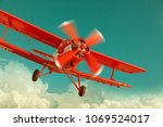 Red Biplane Flying In The...