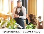 girl looking at a food menu at... | Shutterstock . vector #1069557179