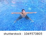 thai man swimming in the pool | Shutterstock . vector #1069573805