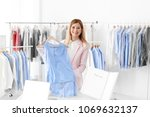 young woman holding hanger with ... | Shutterstock . vector #1069632137