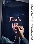"woman writing ""time's up"" on a... 