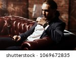 imposing young man sitting on a ... | Shutterstock . vector #1069672835