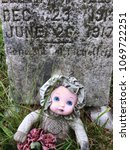 doll sitting in a cemetery | Shutterstock . vector #1069722251