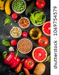 Small photo of Healthy food background, trendy Alkaline diet products - fruits, vegetables, cereals, nuts. oils, dark blue concrete background above