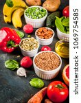 Small photo of Healthy food background, trendy Alkaline diet products - fruits, vegetables, cereals, nuts. oils, dark blue concrete background copy space