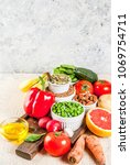 Small photo of Healthy food background, trendy Alkaline diet products - fruits, vegetables, cereals, nuts. oils, light concrete background copy space