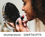 woman putting on lipstick at... | Shutterstock . vector #1069761974
