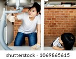 asian family fixing kitchen sink | Shutterstock . vector #1069865615