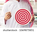 Small photo of Arab man holding a modern target with number 1-10 on cityscape. Concept of objective attainment, achieve business target goal.