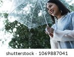 rainy day asian woman wearing a ... | Shutterstock . vector #1069887041