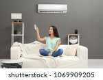 Small photo of Young woman switching on air conditioner while sitting on sofa at home