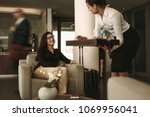 woman sitting at airport lounge ... | Shutterstock . vector #1069956041