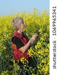 Small photo of Female agronomist or farmer examining blossoming canola field using tablet, rapeseed plant in early spring