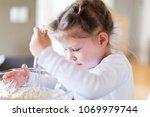 little girl mixing dough for... | Shutterstock . vector #1069979744