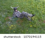 Small photo of A lady disguised as a bull in a disgusting disguise and a mask with horns lies on a meadow, floral spring grass. Child theatre, outdoor perform.
