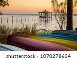A lone brown pelicanon a post at sunset with colorful canoes on the shore of Mobile Bay, at Fairhope Alabama
