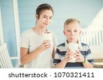 two cute kids drinking... | Shutterstock . vector #1070321411