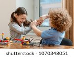 boy and girl fighting over toys.... | Shutterstock . vector #1070348051