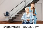 senior and nurse in the house... | Shutterstock . vector #1070373494