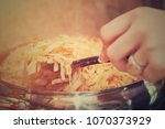 Small photo of Woman stirrings vegetable cabbage stew in the frying pan with the stir spoon. Healthy homemade eating.