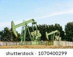 two active pumpjacks pumping... | Shutterstock . vector #1070400299