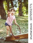 Small photo of Little girl playing on the teeter in nature