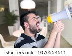 portrait of young man shouting... | Shutterstock . vector #1070554511