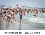 AVON, NEW JERSEY/USA - JULY 7: Big crowds of sunbathers seek relief from the week long heatwave enjoying the surf on July 7, 2012 at the beach in Avon NJ. - stock photo