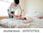 baby has had her nappy changed... | Shutterstock . vector #1070727521