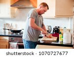 mature man is cooking in the... | Shutterstock . vector #1070727677