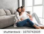 image of smiling couple sitting ... | Shutterstock . vector #1070742035