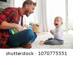 father plays ukulele looking at ... | Shutterstock . vector #1070775551